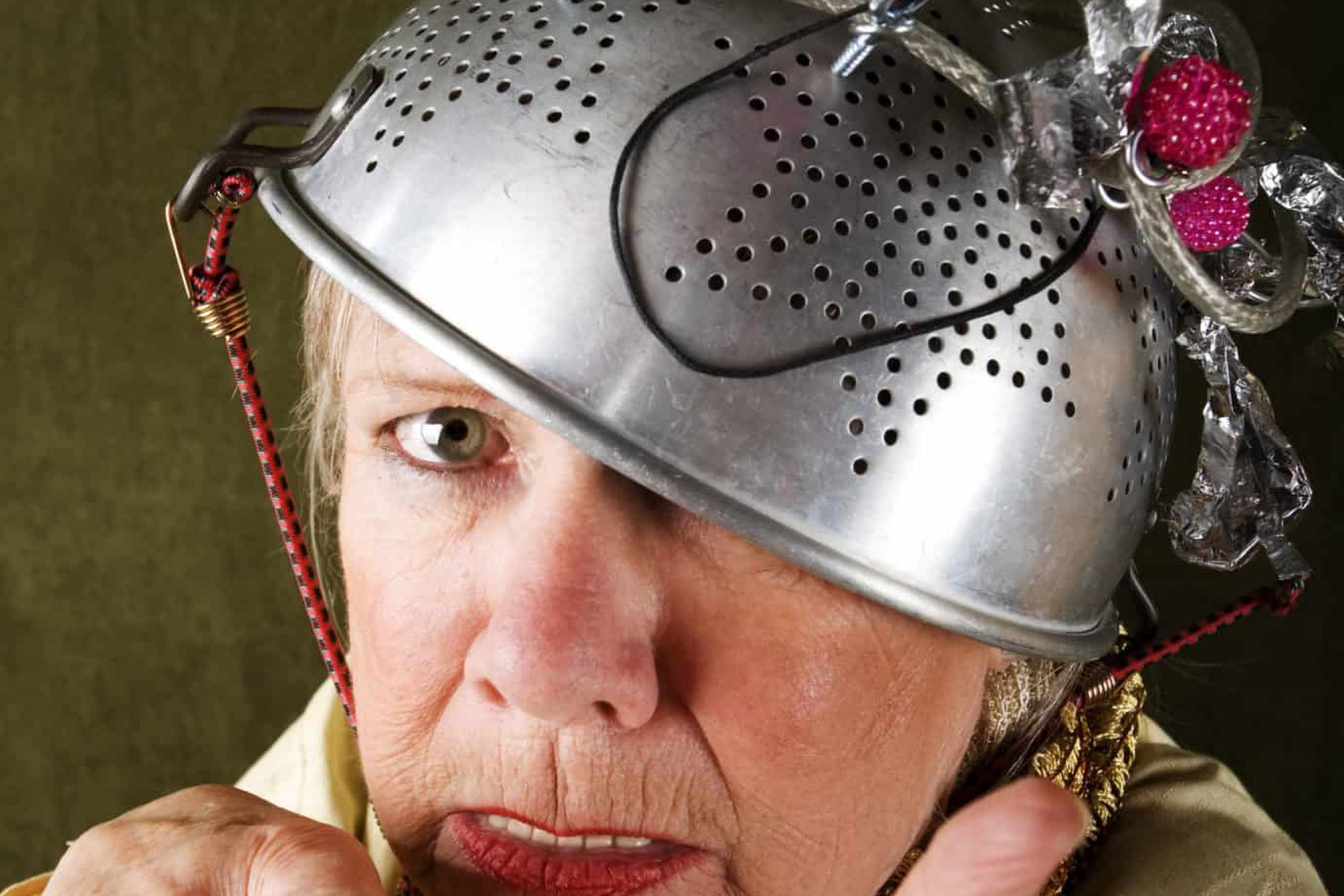 Crazy woman wearing a metal colander for a helmet